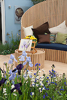 Painting in the garden, with easel, watercolor, irises, large wooden bench seat and table furniture next to house, in pretty blue tones for lovely deck landscaping
