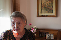 Switzerland. Canton Ticino. Sala. Elsy (Elsa) Hofer Ferrari Ramuz is 86 years old. She seats at home on a chair in her living room. Elsy Hofer Ferrari Ramuz is the niece of Charles-Ferdinand Ramuz (September 24, 1878 – May 23, 1947) who was a French-speaking Swiss writer.  14.11.2017 © 2017 Didier Ruef