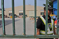A security guard stands in front of the closed factory gates belonging to Smart Union, one of several factories in Zhang Mutou in South China that went bankrupt in the current credit crisis. Smart Union, that produced toys for Mattel amongst others, left 6,000 workers jobless and penniless after they could not pay the salaries. Hundreds of factories in South China are closing due to increased labor and material costs and the current credit crissis is exasperating. The problem leaving ghost towns behind. .24 Oct 2008