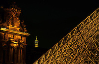 The Louvre Pyramid illuminated at night, with the tip of the Eiffel Tower in the distance, Paris, France.