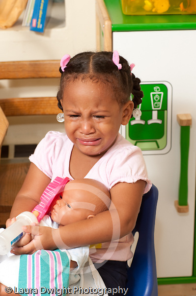 Education Preschool first days of school 2-3 year olds sad girl sitting and crying in classroom doll in her lap