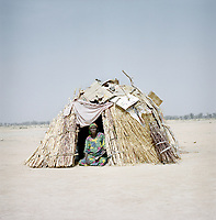 A woman sits in the doorway of a shelter at an unnamed IDP camp housing around 2000 people who have fled the same village near the border with Nigeria. <br /> <br /> When people first arrived here they didn't have anything. They had no clothes. They hadn't eaten for two or three days and had no water to drink. The children were traumatised. The ICRC came here and distributed basic essentials, such as jerry cans, clothes, kitchen tools, emergency kits and food.