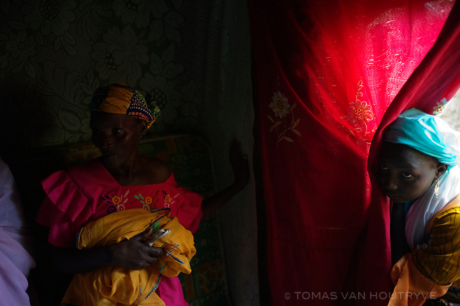 A woman peers past a curtain inside a home on the outskirts of Maradi, Niger on Sept. 25, 2010. The population of Niger is hit yearly with a chronic food crisis that generally peaks between May and September.