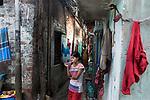 A young girl brushes her teeth at Maniktola slum in Kolkata during 21 days lock down in India due to covid 19 pandemic. Kolkata, West Bengal, India. Arindam Mukherjee.