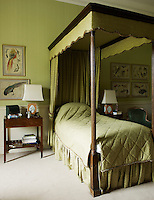 A guest bedroom is furnished with a single four-poster bed and decorated with framed watercolours of birds