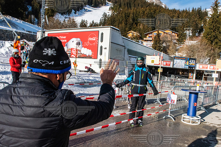 A skier being ordered by an employee, surveying the movement of people at the base of the ski lifts, to follow the extra rules put in place due to COVID-19 restrictions.