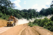 La Gongue, Gabon. Renault trucks loaded with Okume tree trunks on a dirt road.