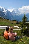 CHE, Schweiz, Kanton Bern, Berner Oberland, Grindelwald: Grosse Scheidegg - Blick auf die Gipfel von Eiger (3.970 m) mit Eigernordwand und Moench (4.107 m) - Paar sitzt in Blumenwiese | CHE, Switzerland, Canton Bern, Bernese Oberland, Grindelwald: Grosse Scheidegg - view at peaks of Eiger (3.970 m) with Eiger-Northface and Moench (4.107 m) - couple sitting in flower meadow