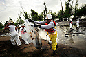 Workers continue the oil cleanup on the Mississippi River in Jesuit Bend, Louisiana 25 July 2008. A ship collided with an oil barge spilling thousands of barrels of fuel oil 23 July 2008 forcing the closure of the river 100 miles from New Orleans to the Gulf of Mexico..
