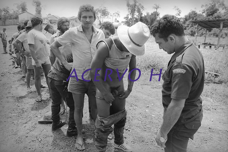 Garimpeiro preso, é revistado, por policial militar após confronto na empresa OCA Mineração.<br /> Xingu<br /> © Paulo Santos<br /> 1984.