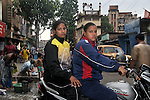 INDIA (West Bengal - Calcutta), August 2010,Shakila Babe(front) and Sanno Babe (back) on a motorbike in their locality. Shakila and Shanno are twins from a poor muslim family of Iqbalpur, Kolkata. . Inspite of their late father's unwillingness to send his daughters to take up  boxing her mother Banno Begum inspired them to take up boxing at the age of 3. Their father was more concerned about the social stigma they have in their community regarding women coming into sports or doing anything which may show disrespect to the religious emotions of his community. Shakila now has been recognised as one of the best young woman boxers of the country after she won the  international championship at Turkey in the junior category. Shanno is also been called for the National camp this year. Presently Shakila and shanno has become the role model in the Iqbalpur area  and parents from muslim community of Iqbalpur have started showing interst in boxing. Iqbalpur is a poor muslim dominated area mostly covered with shanty town with all odds which comes along with poverty and lack of education. - Arindam Mukherjee
