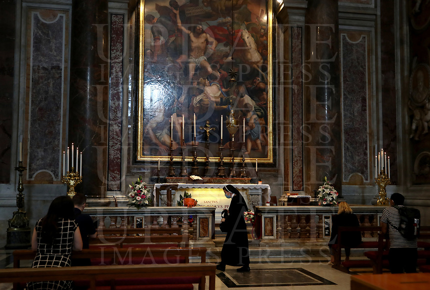 People pray by the tomb of late Pope John Paul II on the 100th anniversary of his birth, in St. Peter's Basilica on May 18, 2020 at the Vatican in the day of its reopening. Italy is slowly lifting sanitary restrictions after a two-month coronavirus lockdown.<br /> UPDATE IMAGES PRESS/Isabella Bonotto<br /> <br /> STRICTLY ONLY FOR EDITORIAL USE