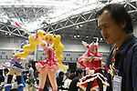 "May 3, 2010 - Tokyo, Japan - A pedestrian walks past posters on display during the Treasure Festa 2010 at Tokyo Big Sight, Japan, on May 4, 2010. Some visitors and hobbyists concentrate specifically on a certain type of figure, such as garage kits, gashapon, or PVC bishojo (pretty girl) statues. According to many who study the phenomenon, many 'figure moe zoku', a Japanese term which refers to ""Otaku who collect figurines"", have difficulty in navigating modern romantic life and prefer to go on ""dates"" with their favorite figurine during off hours."