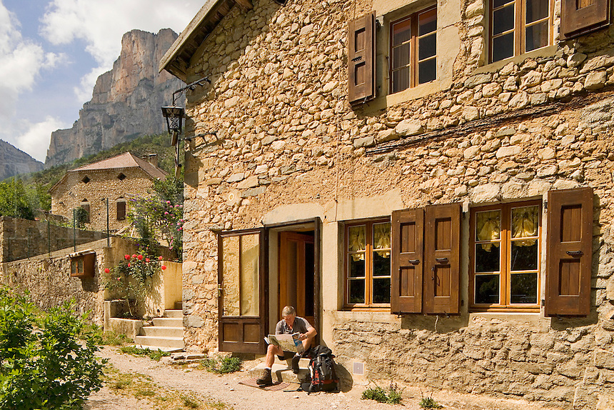 France. Drome. Diois. Walker reading map on doorstep of Gite Rural at Archiane in the Cirque d'Archiane.