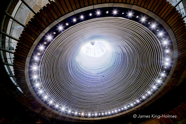 Looking up at the cowl and funnel of the Senedd of the National Assembly for Wales, Cardiff. Besides acting as an indirect lighting feature, the cowl is a free rotating structure and is wind-driven to provide ventilation to the chamber.