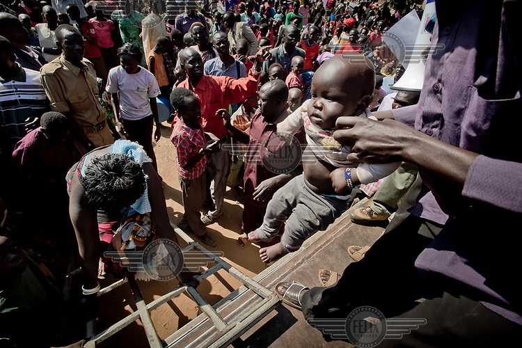 A baby is lifted on board a truck which will drive his family to Nyumanzi settlement, a few kilometres from Dzaipi where South Sudanese refugees are being resettled on plots of land.
