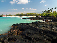 A view of a state beach from the lava rock surrounding it, Big Island.