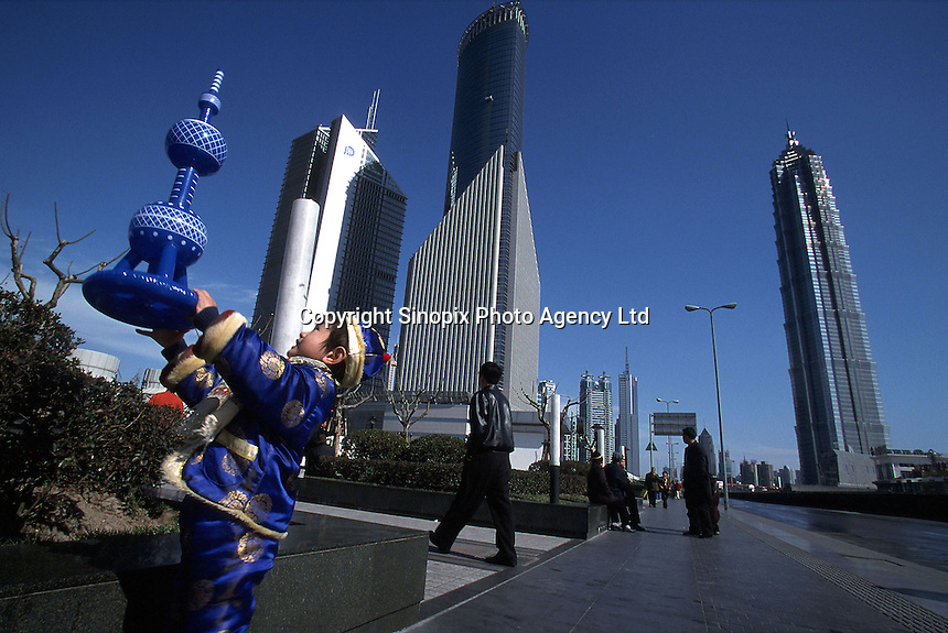 With the high rises of Shanghai's Pudong Financial District in the background, a young boy in traditional new year clothing raises a blow-up model of the Oriental Pearl TV Tower..23-FEB-02