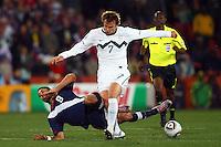 Nejc Peknic of Slovenia tackles Clint Dempsey of USA