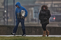 WEATHER PICTURE WALES<br /> Pictured: A man and a woman walk against the wind and rain in Porthcawl, south Wales, UK. Tuesday 18 December 2018<br /> Re: Heavy rain has been forecast for much of the day in areas of south, west and parts of mid Wales with the Met Office having issued a yellow warning.<br /> Wind gusts along the coast are expected to reach up to 65 mph, while in inland areas they could reach 50 mph.