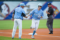 Brian Miller (5) of the North Carolina Tar Heels shakes hands with head coach Mike Fox as he rounds third base after hitting a home run against the North Carolina State Wolfpack in Game Twelve of the 2017 ACC Baseball Championship at Louisville Slugger Field on May 26, 2017 in Louisville, Kentucky.  The Tar Heels defeated the Wolfpack 12-4 to advance to the semi-finals.  (Brian Westerholt/Four Seam Images)