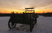 The silhouette of a wagon at Wagon Hill Farm in Durham, New Hampshire at sunset during the winter months.