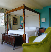 A contemporary interpretation of the traditional mahogany four-poster bed in a low-ceilinged room