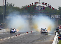 Aug 31, 2014; Clermont, IN, USA; NHRA funny car driver Courtney Force (right) and teammate Robert Hight smoke the tires during a peddle fest at the US Nationals at Lucas Oil Raceway. Mandatory Credit: Mark J. Rebilas-USA TODAY Sports