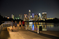 A perfect night for a stroll and take the dog for a walk on the Board Walk Trail Bridge on Lady Bird Lake with a colorful reflection of the downtown Austin skyline reflecting on the calm lake waters. The trail joins 10 miles of trails border Lady Bird Lake in downtown Austin and serve as a social hub for runners, walkers and cyclists. - Stock Image.