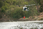 Cal Fire and local government crews from East Bay MUD and Moke Hill, along with airtankers and helicopters fight an 60 acre wildland fire near the Middle Bar Bridge over the Mokelumne River, Calaveras County, Calif...Roger's Helicopters Bell 212 dips water from Lake Pardee