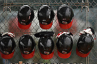 Illinois State Redbirds helmets hang on the fence during a game against the Georgetown Hoyas on March 7, 2015 at North Charlotte Regional Park in Port Charlotte, Florida.  Illinois State defeated Georgetown 2-1.  (Mike Janes/Four Seam Images)