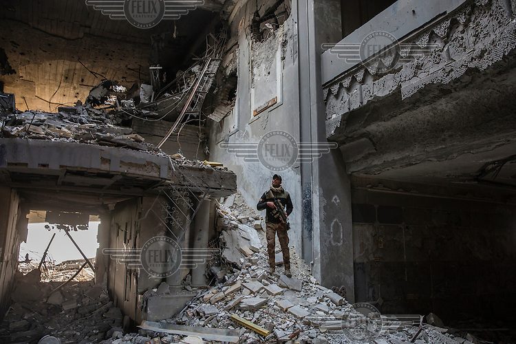 An Iraqi Special Operations Forces soldier  stands amidst the bombed out ruins of a Saddam Hussein era government building that was occupied by Islamic state fighters.<br /> Mosul has been the scene of fierce fighting between militants from Islamic State (IS) and government forces since the beginning of the campaign to retake the city from militant control started in October 2016.