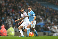 Neil Taylor competes with Jesus Navas during the Barclays Premier League Match between Manchester City and Swansea City played at the Etihad Stadium, Manchester on 12th December 2015