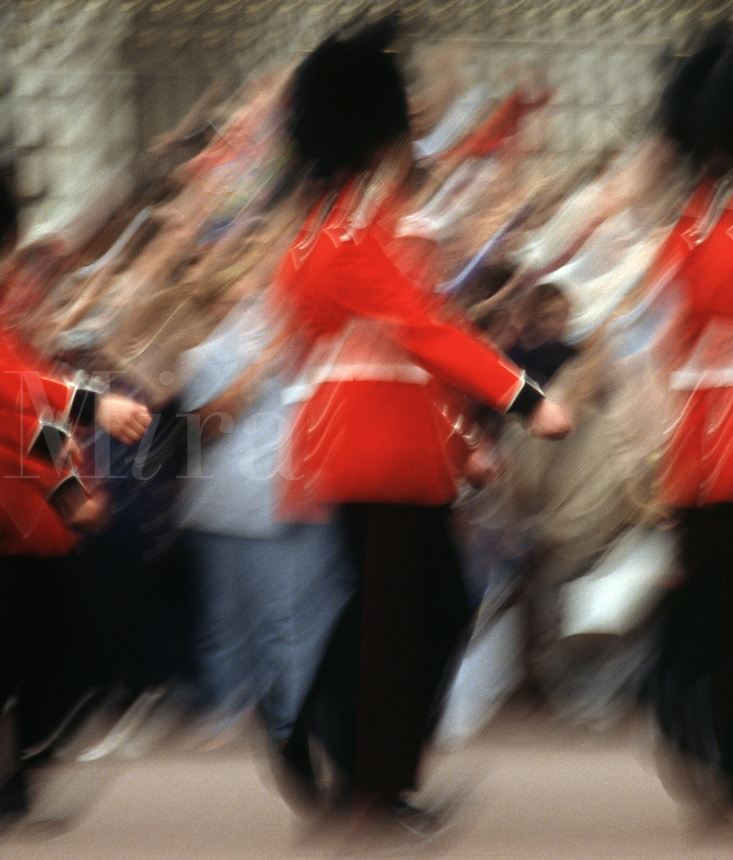 Detailed, blurred motion image of Buckingham Palace Guards in traditional uniforms marching in parade formation as tourists look on. London, England.