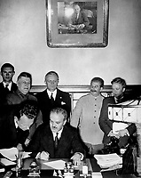 Soviet Foreign Minister Molotov signs the German-Soviet nonaggression pact; Joachim von Ribbentrop and Josef Stalin stand behind him, Moscow, August 23, 1939.  Von Ribbentrop Collection.  (Foreign Records Seized)<br /> NARA FILE #:  242-JRPE-44<br /> WAR & CONFLICT BOOK #:  990