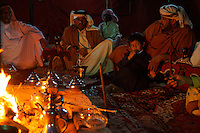 Family around campfire is the Ali Saeed Nasser Al Minhali family. Men and their sons share food and quiet conversation in the evenings in the tent of the family compound.