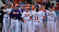 Designated hitter Shane Kennedy (11) of the Clemson Tigers is congratulated for his his game-winning two-run home run in the bottom of the eighth inning in a game against the William & Mary Tribe on Opening Day, Friday, February 15, 2013, at Doug Kingsmore Stadium in Clemson, South Carolina. Clemson won, 2-0. (Tom Priddy/Four Seam Images)
