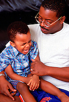 African American father with his son who is having a bit of a temper tantrum.