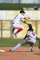 Surprise Saguaros infielder Sean Coyle (2) turns a double play as Daniel Carbonell (9) slides in during an Arizona Fall League game against the Scottsdale Scorpions on October 16, 2014 at Surprise Stadium in Surprise, Arizona.  Surprise defeated Scottsdale 7-3.  (Mike Janes/Four Seam Images)