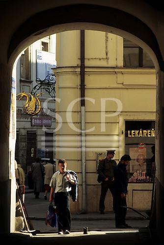 Bratislava, Slovakia. Soldier, workman, man carrying plastic carrier bag through an arch.