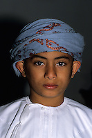 Mudayrib, Oman, Arabian Peninsula, Middle East - Omani boy of the al-Harthy tribe.  He is wearing a white dishdasha, and a blue msarr, or massar, around his head.  A white tassel several inches long, called a kashkusha or a frakha, hangs from the right side of his neckline.  The kashkusha is often perfumed.
