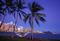Couple kissing in hammock between palm trees, with Waikiki and Diamond Head in background