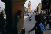A woman peers out onto the street, La Catedral in the background of the archways during a bustling lunchtime scene at Plaza De Armas. Peru's capital city, Lima with a present-day population of, 24 million residents was founded by Pizarro in 1535.