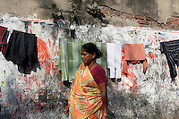A woman passes by a line of drying clothes in Kolkata.<br />