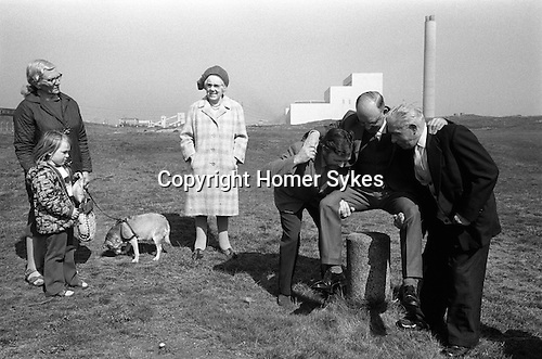 Dunting the Freeholder, Newbiggin by the Sea. Northumberland  1974. Vandalised Moot Stone now use a small concrete pillar. A new freeholder is Dunted.<br /> Lynemouth Power Station in background.