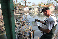 Brett Huff, of the Humane Society of Missouri, checks his list of homes to be searched while looking for surviving pets in New Orleans three weeks after Hurricane Katrina destroyed the city. Animal rescue teams conducted their searches in excruciating heat and physically challenging conditions. 9/19/05 Julia Cumes