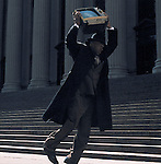 Man in suit throwing television