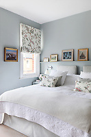 A double bed in a traditional bedroom painted a pale grey. A roman blind in a floral pattern fabric matches two cushions placed on the bed. Two upholstered cushions act as a headboard.