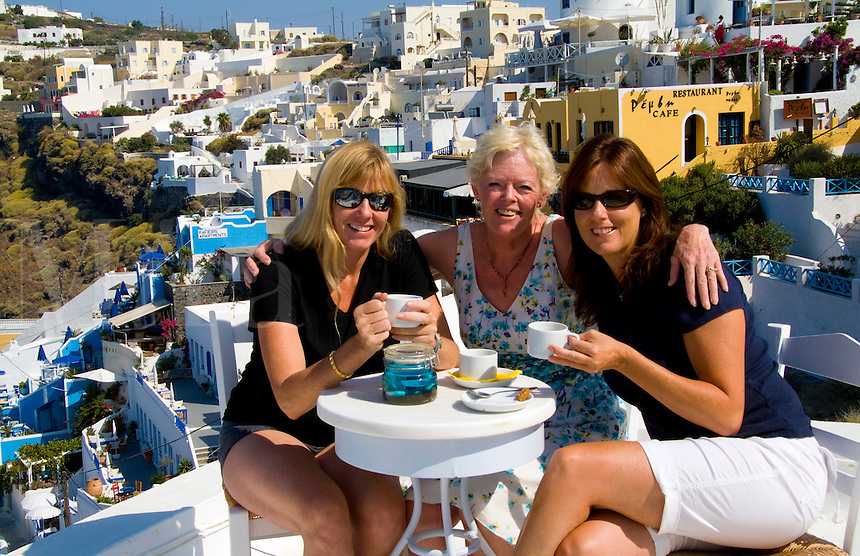Santorini Greece and the beautiful white buildings on the mountain cliffs of main city of Fira and three woman tourists relaxing with drinks on roof