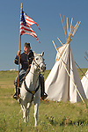 A US Calvary soldier sits horseback and holds the American flag during the annual reenactment of the Custer Battlefield or the Little Bighorn at Hardin, Montana